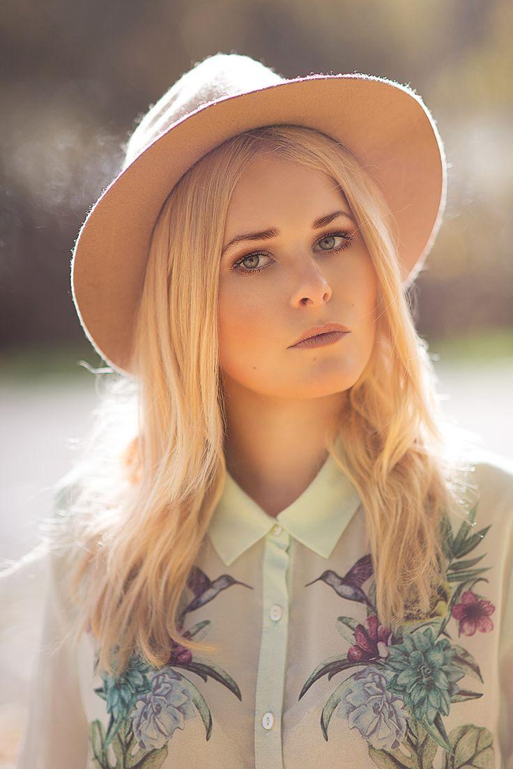 Portrait von Christina Key, die eine schöne Bluse mit Floralmuster und einen Hut in beige trägt
