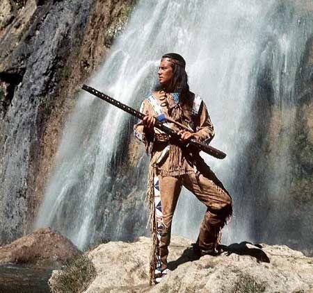 Winnetou | Pierre Brice als Winnetou mit Gewehr vor einem Wasserfall.