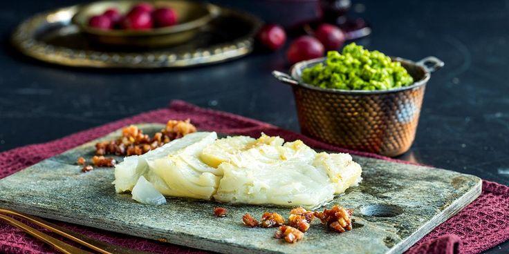 Lutefisk klar til servering med ertestuing og baconterninger