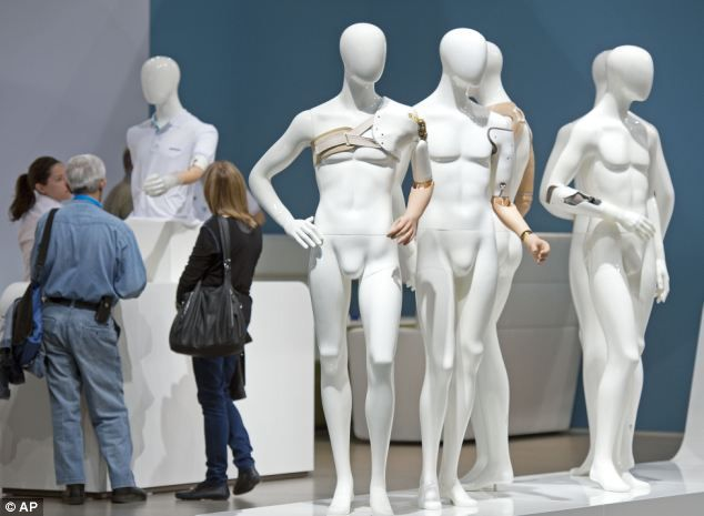 Visitors stand besides dummies with upper limb prosthetics during the opening day at the trade show.