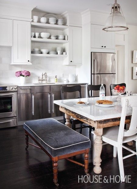 Weathered furniture keeps this cottage from looking too formal.~~This weekend home's open-concept space pairs a vintage farmhouse-style dining table with a contemporary kitchen. Stainless-steel cabinets and dark-stained pine floors break up the expanse of white. A bench reupholstered in mohair adds a touch of cosy luxury.