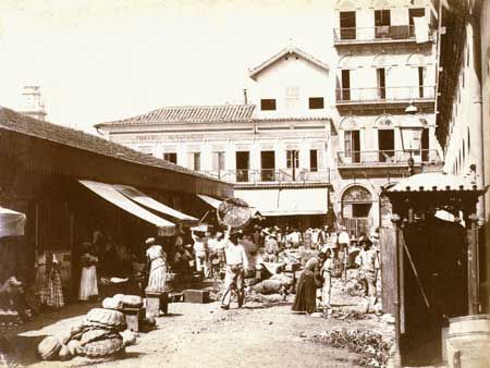 Mercado da Praia do Peixe, aproximadamente 1893/1894. O movimento do comercio em frente ao mercado. Ao fundo, o predio do Hotel Machado. À  esquerda, uma das torres da Igreja de Nossa Senhora do Monte do Carmo.