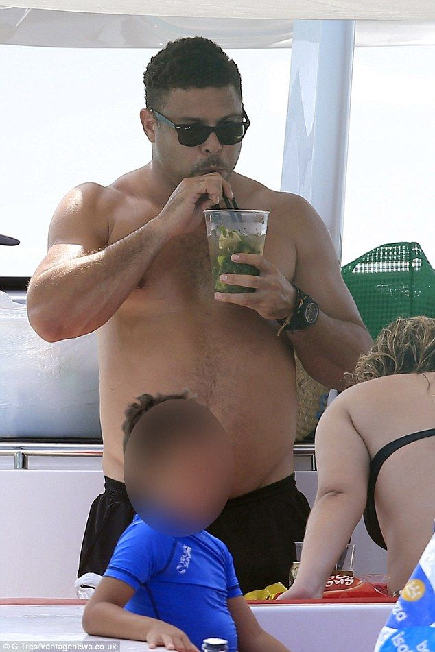 Cocktail time: The sports star cooled down with a large mojito after his dip in the ocean