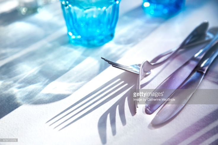a close up of cutlery and pale blue glasses on white table cloth in sunshine