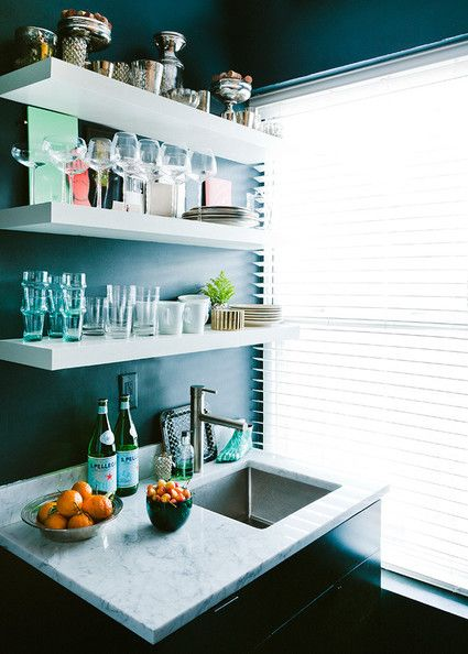 Interior designer Samuel Masters employed open shelving for the modest kitchen of his 400-square foot apartment, highlighting classic glassware as decor.