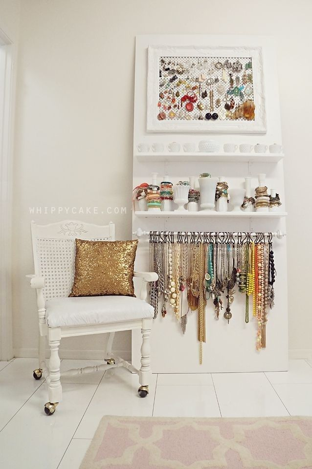 Jewelry storage. Earrings on a mesh screen inside a frame, bracelets stacked on the necks of bottles and vases, and necklaces hung on S-hooks from a curtain rod.