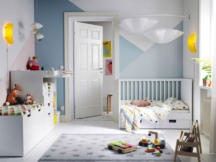 Dormitorio infantil con una cuna blanca con dos cajones, un cambiador y un banco con un cajón grande con ruedas.