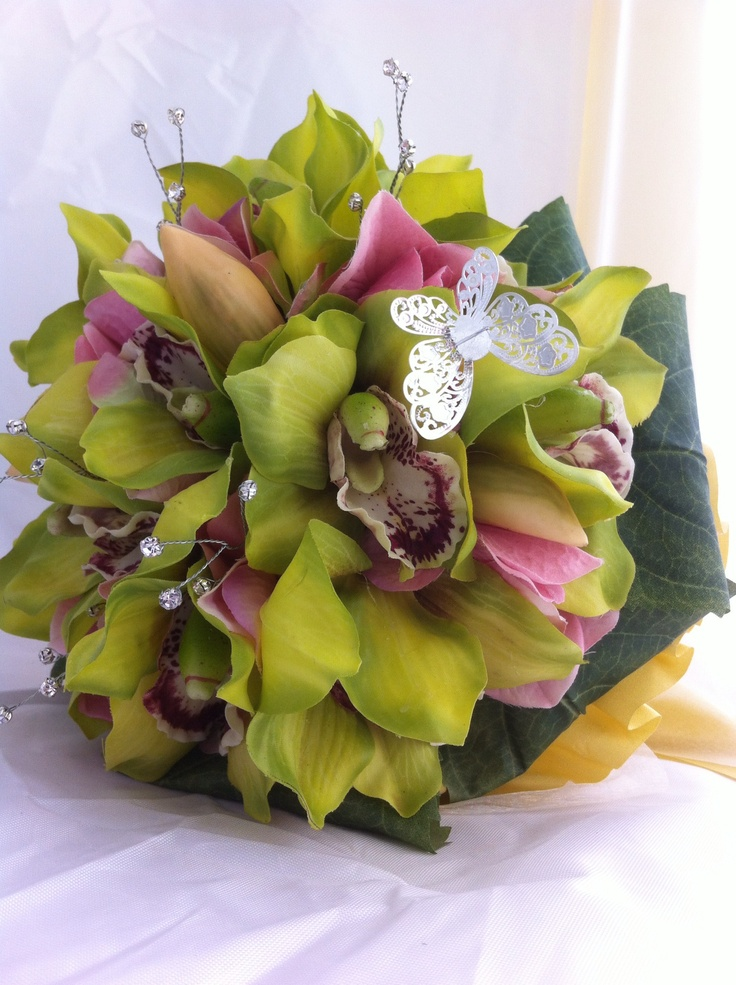Cymbidium orchids, hydrangeas and crystals forms the head of this bouquet with a silver butterfly fluttering above.