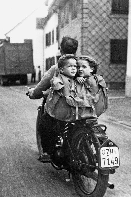 Schwarz-Weiss-Bild: Ein Mann auf einem Motorrad, auf dem Gepäckträger eine Tasche, in der ein Knabe und ein Mädchen sitzen.