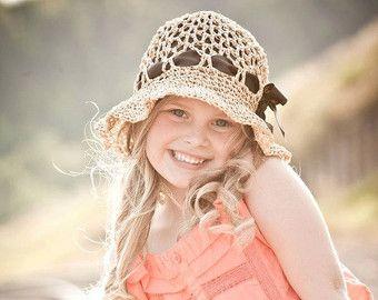 menina loira sorrindo com chapeu de croche bege cm fita marron