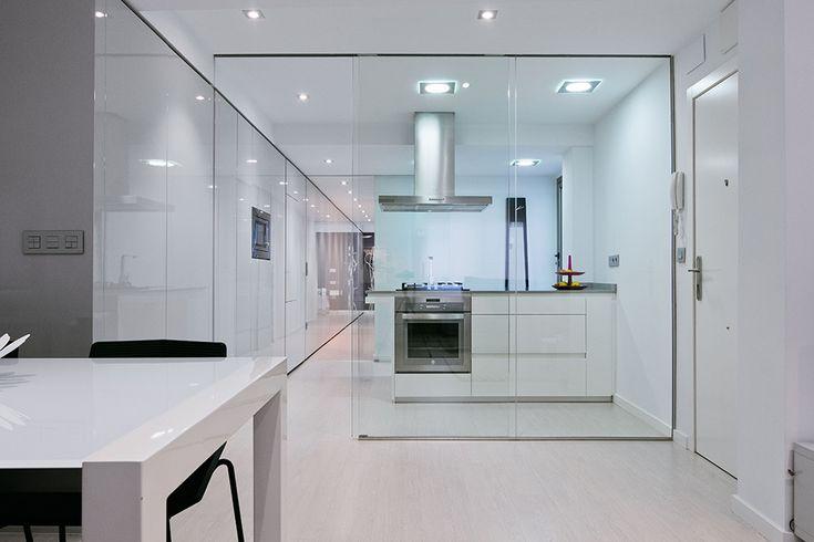 Chiralt Arquitectos I Comedor-cocina en vivienda moderna con mobiliario minimalista separados por un cristal, dando luz y sensación de espacio.