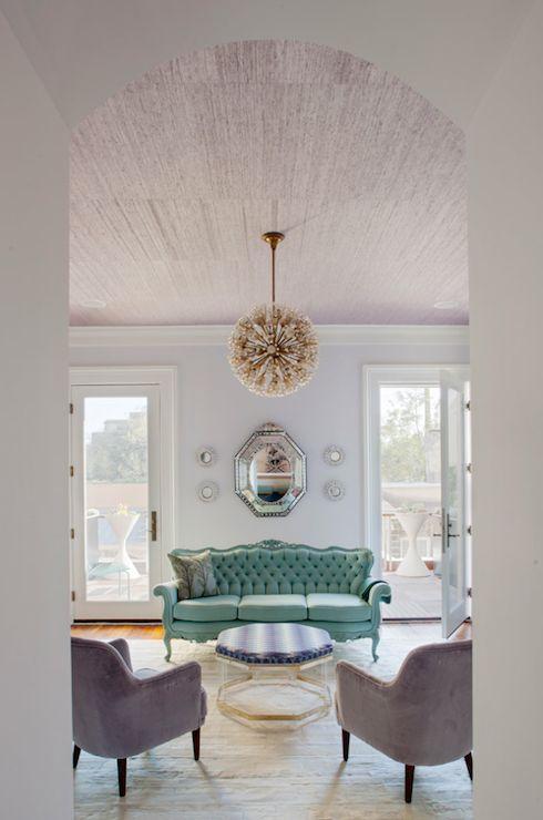 Rethink Design Studio - living rooms - lavender walls, venetian mirror, silver sunburst mirrors, gold orb pendant, tufted turquoise sofa,  gold framed hexagonal ottoman, hardwood floors, pink grasscloth ceiling