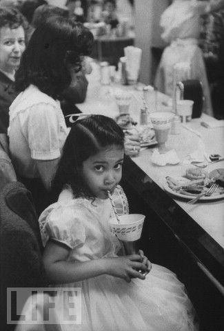 a young african american girl sitting at an integrated lunch counter.
