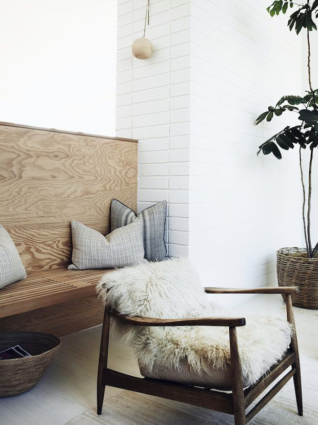Cosy up a wooden-framed chair with a textured cushion or throw