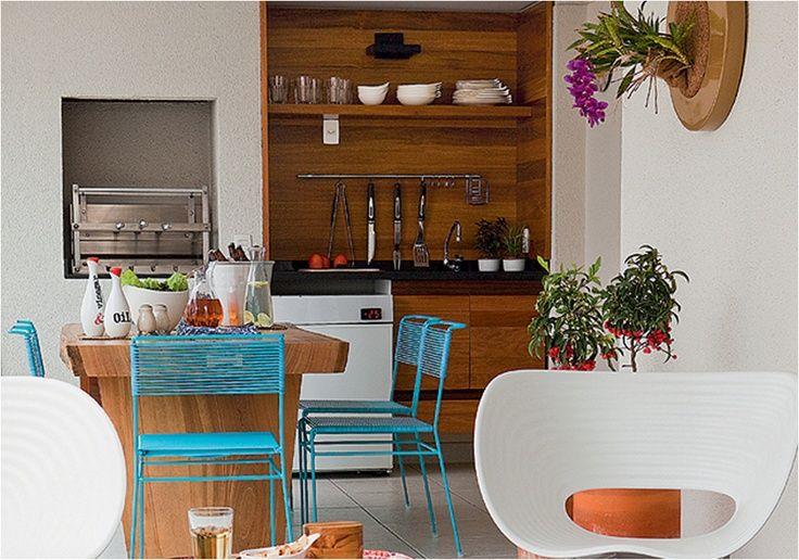 Piso e churrasqueira claros - Bancada e marcenaria escuras - Cadeiras coloridas