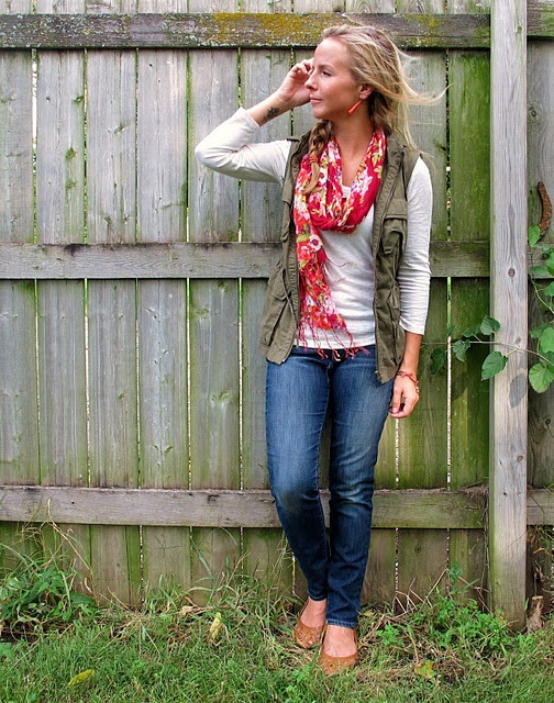 red scarf, olive vest, white 3/4 sleeve, jeans, windswept