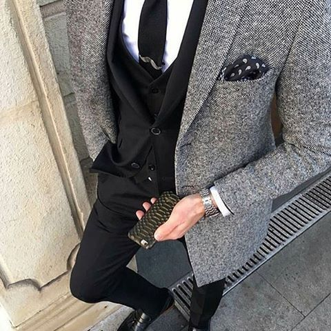Something as simple as opting for a black three piece suit and a grey tweed blazer jacket can potentially set you apart from the crowd. If you don't want to go all out formal, make black leather tassel loafers your footwear choice.   Shop this look on Lookastic: https://lookastic.com/men/looks/three-piece-suit-blazer-dress-shirt/24062   — Black Tie  — White Dress Shirt  — Black and White Paisley Pocket Square  — Black Three Piece Suit  — Grey Tweed Blazer  — Silver Watch  — Black Leather…