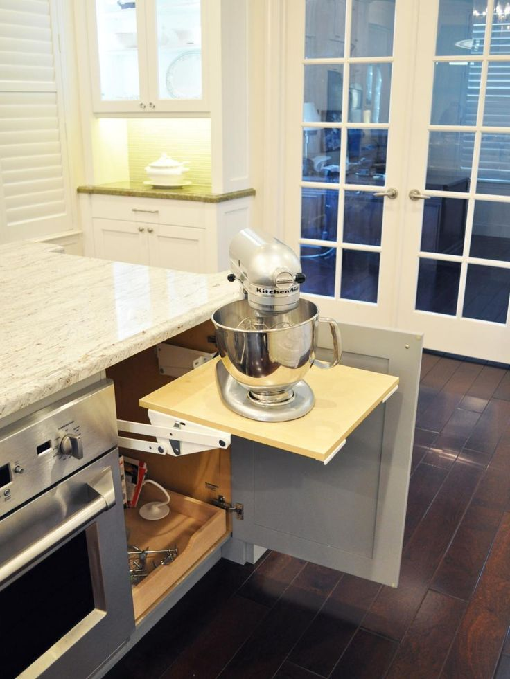 The large island in this kitchen is an all-in-one baking station with a single oven, prep sink and lowered counter. The final element of the baking station is this pop-up mixer stand that saves counter space and makes storing the appliance between uses a breeze.