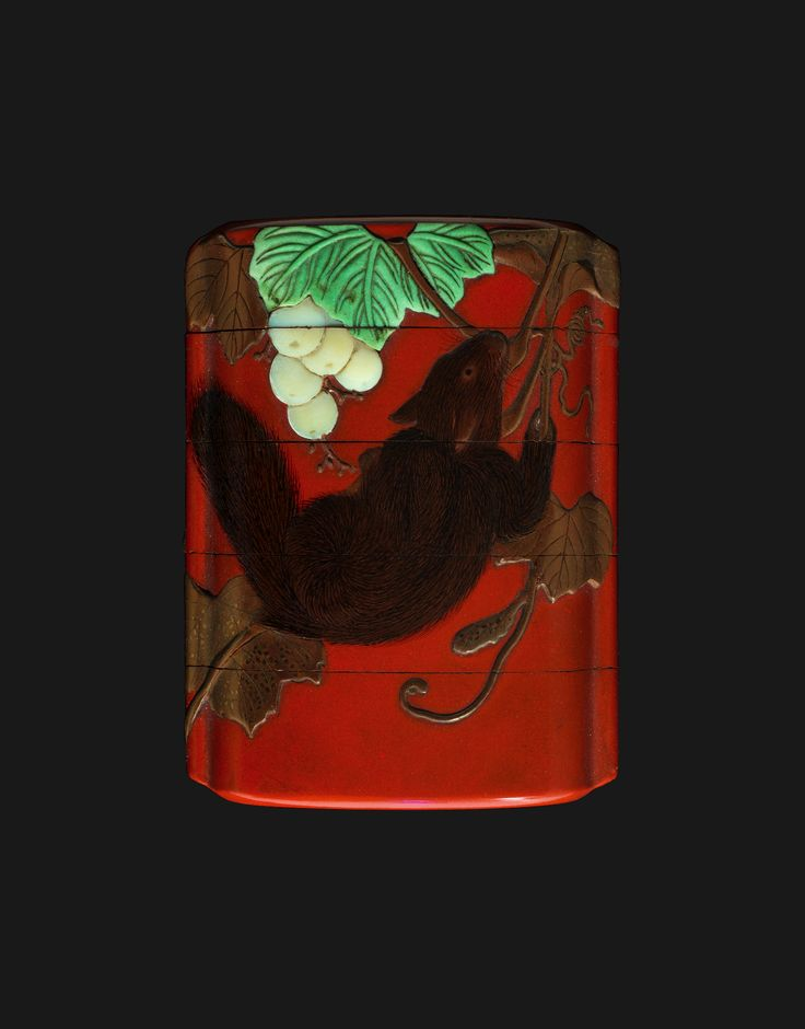 INRŌ HARA YOYUSAI (1772-1845) This red lacquer inrō has four cases or compartments and is signed by Yoyusai. The decoration covers the entire surface and depicts a squirrel in relief hanging from a vine that has bunches of grapes in mother-of-pearl and some leaves in green-tinged ivory while others are in gold hiramakie (flat sprinkled painting).