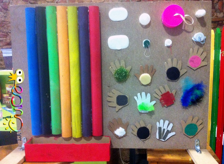 "Fun sensory & motor skill panel - post corks & pom-poms through the pipes, touch the different textures, twist & unscrew lids & identify colours ("",)"