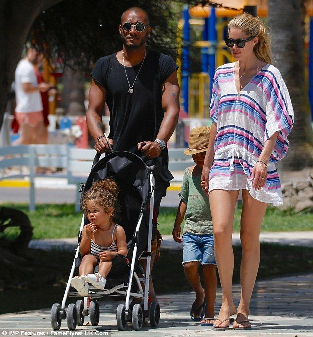 Doting on their children: Leading her five-year-old son, Phyllon, by the hand, Doutzen loo...