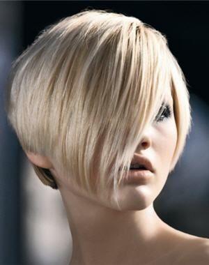 Les cheveux de cette femme ont été coupés court et séparés par une raie d'un côté. Pour créer un contraste, son coiffeur a laissé les cheveux du devant très longs et les a coiffés en les balayant sur son visage. Il a taillé cette longue mèche en suivant sa mâchoire. La coloration blond pâle est rehaussée par quelques mèches plus foncées.