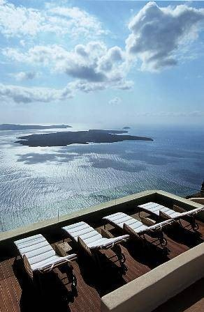 Stand between the crystal waters of the Aegean Sea and the blue Greek sky at Icons Hotel, in Santorini