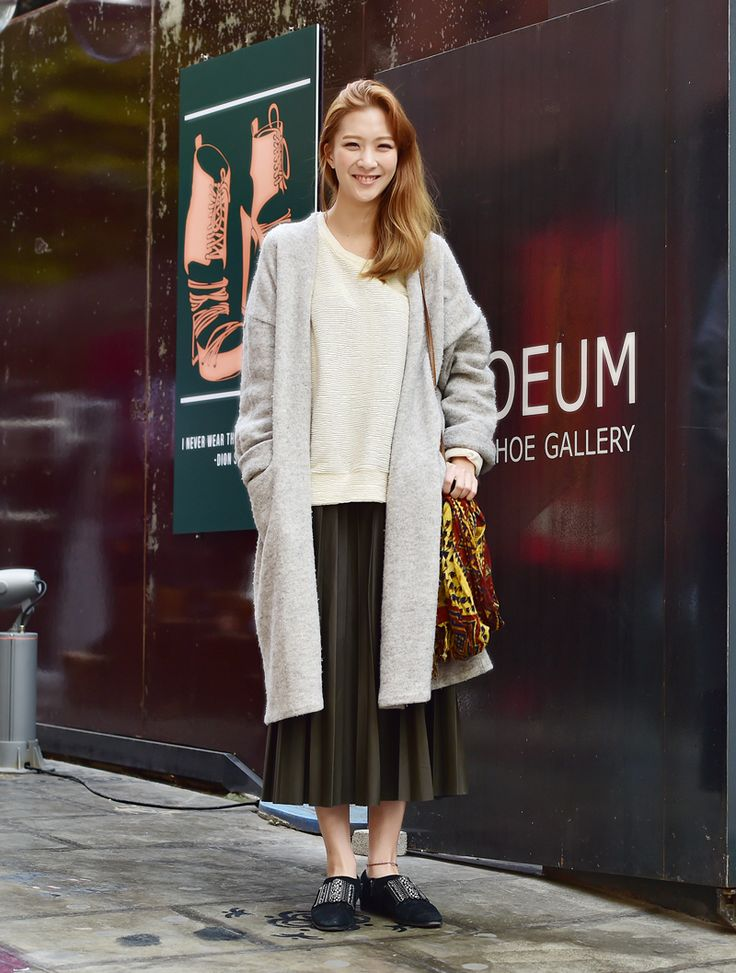 Is it the bright smile of her or her fashion sense of matching over sized long cardigan, crewneck shirts and tulle skirt that makes her look stunning?  Paisley pattern print fabric bag and stud flat shoes have some how similar feel to it.   Great modern hippie look !