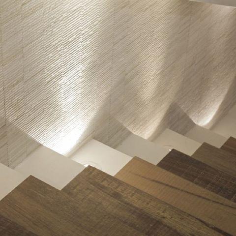 Escada com parede em mosaico e degraus em porcelanato Simplesmente Branco e Madeira.