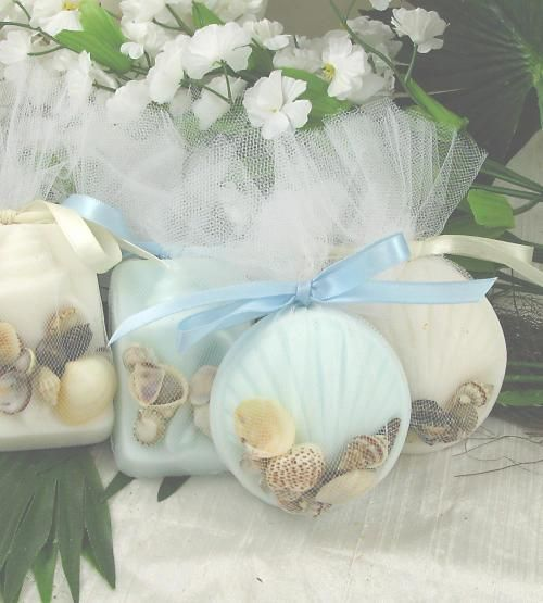 Seashell Soap Wedding Favor features a round seashell design and a rectangular conch shell design. It is available in white with a coconut scent or blue with a sea breeze. Packaged in white tulle with real seashells.