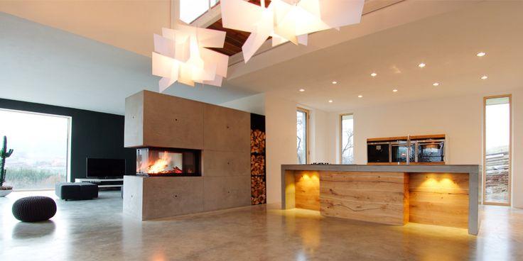 Ein Kaminofen als Raumteiler nutzen. Kühler Sichtbeton verbindet sich mit der warmen Ausstrahlung einer Feuerstelle. Würde Dir das gefallen?