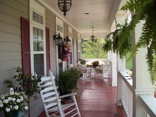 Pretty porch, I like the red floor and shutters. The greenery and seating make it inviting.