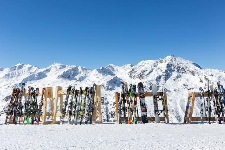A line of skis and snowboards stored on racks outside a cafe on the slopes at Hochgurgl with the Otztal Alps in the background.