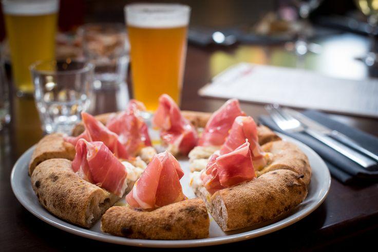 Pizza bianca con prosciutto, burrata e olio all'arancia: