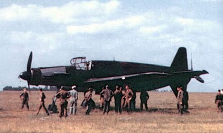 color picture of the Dornier Do 335 at rest; note size compared to personnel