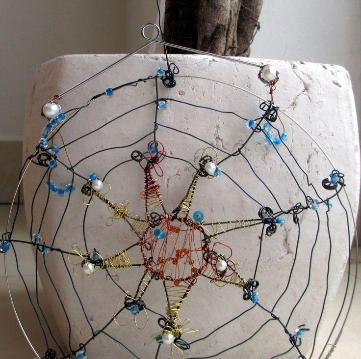 """Pavučinka ,,Sun"""" Další z řady nedokonalých pavučinek, které osvěží váš interier, zvlášť když svítí sluníčko, nebo je máte pověšené na svítidle. Pavučinku /prům. 14cm/ tvoří paměťový drát, různé drátky a korálky. Součástí je pevný drátek na zavěšení. Respektujte prosím autorská práva"""