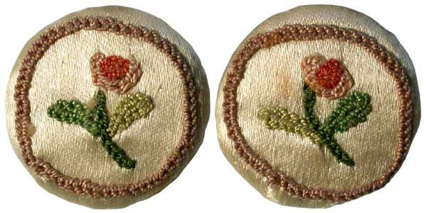 a pair of 18th century ivory silk waistcoat buttons embroidered in coloured threads with a rose stem within a mushroom coloured circular border
