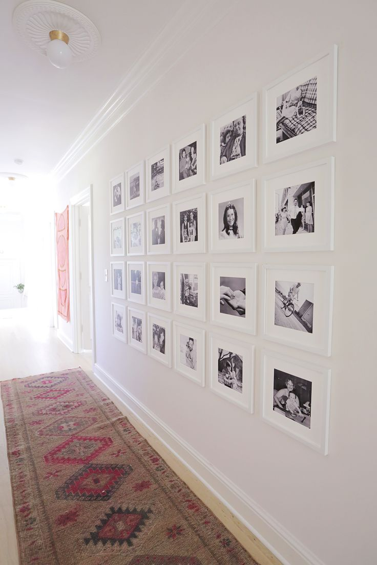 Family photo gallery wall feels classy because they're all the same frame, the have wide mattes, and they're all black and white.