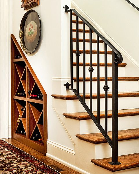 Traditional wine cellar below wrought iron stair railing