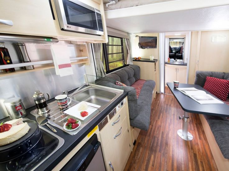 A view of the Avida Leura motorhome interior from toward the front of the vehicle to the rear with the electric roll down bed in a raised position. The colour scheme pictured is Scarlet Sunset.