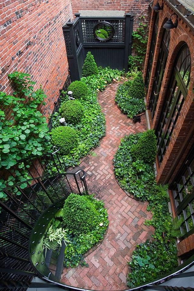 Curvy brick path, flanked by greenery.