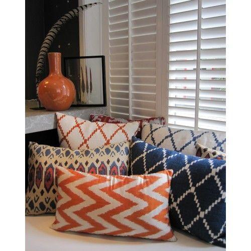 Oranje en blauwe kussens in geometrische patronen. Lekker hoekje zo.