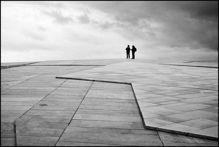 Oslo Opera House; The roof of the building angles to ground level creating a large plaza inviting pedestrians to walk up and enjoy the panoramic views of Oslo. The angles and paving materials are also skateboard-friendly allowing skateboarders to use some areas.  While much of the building is covered in white granite and La Facciata, a white Italian marble, the stage tower is clad in white aluminum in a design by Løvaas & Wagle evoking old weaving patterns. (photo by Kim Erlandsen)