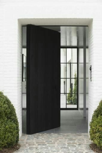 This oversized black pivot door makes a dramatic entryway! Find out more about pivot doors, OR design your own at http://www.pivotdoorcompany.com/Exterior-Doors/.