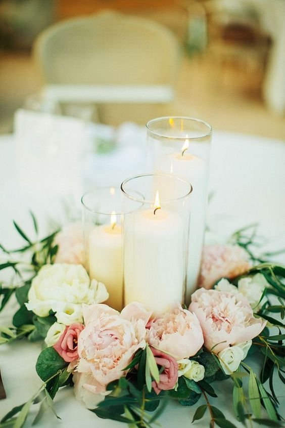 Beautiful wedding centerpiece made of candles in cylinder vases and pastel pink…