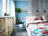 White bed with multicoloured quilt cover/pillowcases and dark turquoise coffee table