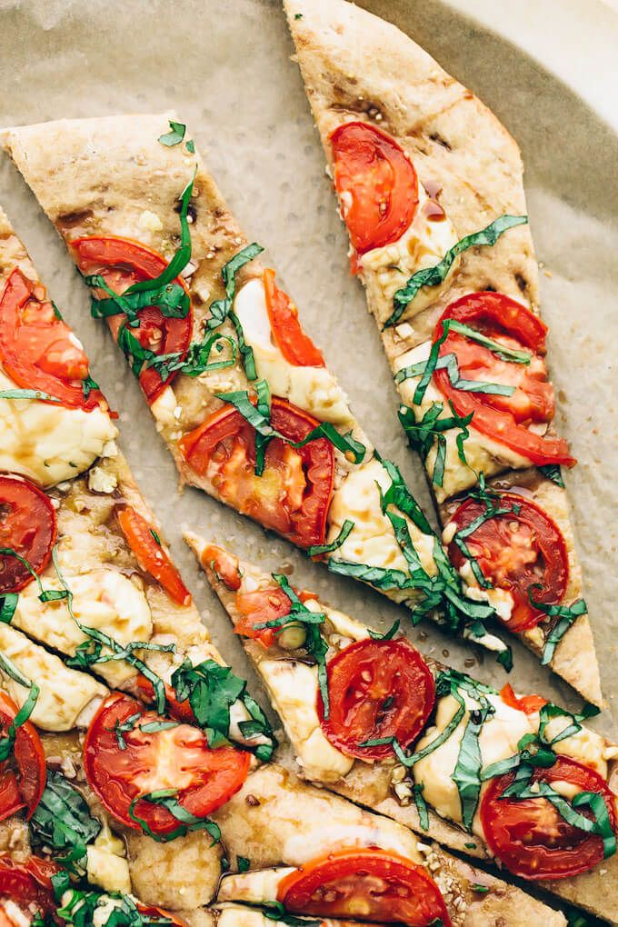 Vegan Caprese Pizza | Crisp, bubbly pizza crust is topped with zesty garlic, tomatoes, homemade cashew mozzarella, balsamic drizzle + lots of fresh basil.