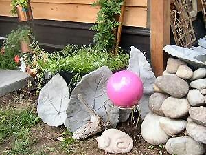garden stuff: pink bowling ball, cement leaves, cement cat