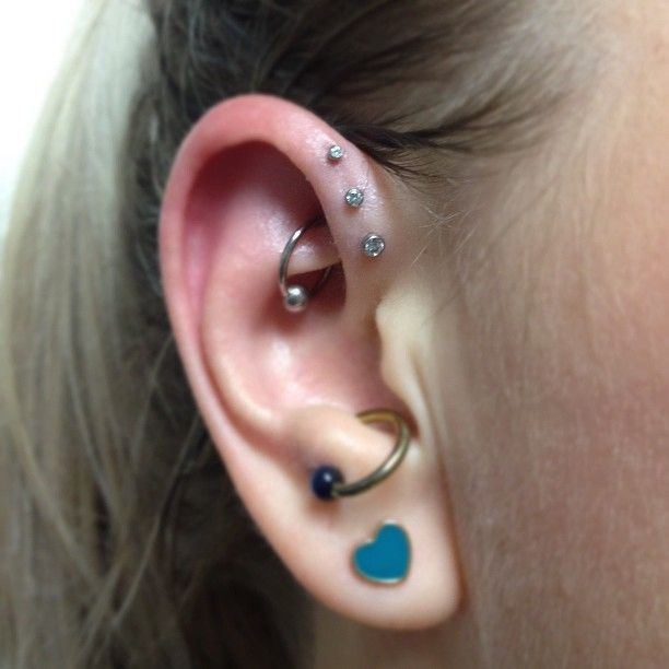 Triple forward helix, done with Neometal threadless labrets. Anti-tragus. Rook.