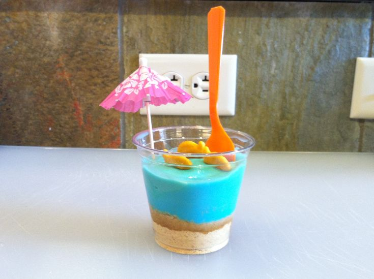Beach cups....crushed graham crackers, vanilla pudding tinted with blue food coloring, gold fish crackers, spoon and umbrella. Fun for pool parties and beach themed parties.